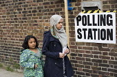 Muslim woman voting in the General Election. Tower Hamlets Polling Station. East London. - Jess Hurd - 2010s,2015,BAME,BAMEs,Black,BME,bmes,campaign,campaigning,CAMPAIGNS,child,CHILDHOOD,children,democracy,diversity,dress,election,elections,electorate,Ethnic,ethnicity,families,family,female,females,Gen