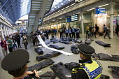 No Borders die-in at St Pancras Eurostar Terminal. Marking the tenth anniversary Frontex, the EU border agency, with body bags representing the 20,000 known migrant deaths at sea. London. - Jess Hurd - 2010s,2015,activist,activists,adult,adults,against,agency,anniversary,Asylum Seeker,Asylum Seeker,bag,bags,BAME,BAMEs,Black,BME,bmes,bodies,body,border,Border and Immigration Agency,CAMPAIGN,campaigne
