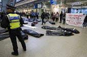 No Borders die-in at St Pancras Eurostar Terminal. Marking the tenth anniversary Frontex, the EU border agency, with body bags representing the 20,000 known migrant deaths at sea. London. - Jess Hurd - 19-05-2015