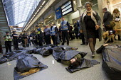 No Borders die-in at St Pancras Eurostar Terminal. Marking the tenth anniversary Frontex, the EU border agency, with body bags representing the 20,000 known migrant deaths at sea. London. - Jess Hurd - 2010s,2015,activist,activists,adult,adults,against,agency,anniversary,anti,Asylum Seeker,Asylum Seeker,bag,bags,BAME,BAMEs,Black,BME,bmes,bodies,body,border,Border and Immigration Agency,CAMPAIGN,camp