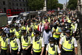 Police escort a small group of fascists alleging the Jewification of Britain. They were banned from Golders Green. Westminster, London. - Jess Hurd - 04-07-2015