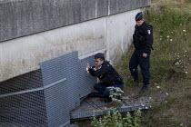 Police search for migrants under a bridge Eurostar Calais Terminal France. - Jess Hurd - 2010s,2015,adult,adults,asylum seeker,asylum seeker,BME black,border,border control,border controls,borders,bridge,CLJ,crisis,detect,detecting,detection,Diaspora,displaced,ethnic,ETHNICITY,eu,Europe,e