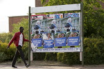Refugee walks past Front National posters. Calais, France. - Jess Hurd - 05-08-2015