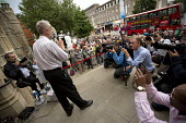 Jeremy Corbyn speaking to overflow of supporters outside Ealing Town Hall before a Quiz Corbyn meeting inside. Bus advertisement reads Defeat The Empire, Join The Rebellion. London. - Jess Hurd - 17-08-2015