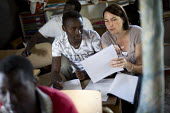 Migrants learn French in a makeshift school. Jenny is a French teacher who volunteers her time to teach in the Calais refugee camp known as The Jungle. France. - Jess Hurd - 2010s,2015,adult adults,adult education,assisting,Asylum Seeker,Asylum Seeker,BME black,camp,camps,class,communicating,communication,Diaspora,displaced,EDU Education,ethnic,ETHNICITY,eu,Europe,europea