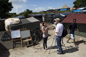 Migrants learn French in a makeshift school. Jenny is a French teacher who volunteers her time to teach in the Calais refugee camp gives an interview to video journalist Jason N Parkinson. France. - Jess Hurd - 04-08-2015