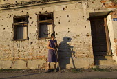 Woman poses for a photograph outside her house riddled with bullets from the war. Tovarnik. Croatia. - Jess Hurd - 23-09-2015