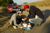 Family changing their baby on the side of the road outside Opatovac refugee camp. Croatia. - Jess Hurd - 2010s,2015,adult,adults,Afghan,afghans,aid,aid agency,assistance,Asylum Seeker,Asylum Seeker,babies,baby,BAME,BAMEs,BME,bmes,border,borders,camp,camps,change,changing,child,CHILDHOOD,children,crisis,C