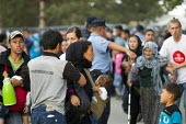Refugees rush to board a bus to Austria after being pepper sprayed by riot police at Opatovac refugee camp. Croatia. - Jess Hurd - 2010s,2015,adult,adults,Afghan,afghans,asylum seeker,asylum seeker,babies,Baby,baby babies,BAME,BAMEs,BME,bmes,border,Border and Immigration Agency,border borders,border control,border controls,border