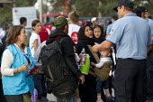 Refugees rush to board a bus to Austria after being pepper sprayed by riot police at Opatovac refugee camp. Croatia. - Jess Hurd - 2010s,2015,adult,adults,Afghan,afghans,argue,arguing,argument,asylum seeker,asylum seeker,babies,Baby,baby babies,BAME,BAMEs,BME,bmes,border,Border and Immigration Agency,border borders,border control