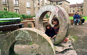 Children and mothers on playground on tenement housing on estate in Possil. Council flats boarded up but most still occupied. Glasgow housing stock due to transfered to housing company - Jess Hurd - 18-09-1999