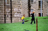 Children playing. Tenement housing on estate in Possil. Council flats boarded up but most still occupied. Glasgow housing stock due to transferred to housing company - Jess Hurd - 18-09-1999