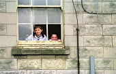 Children looking out of their window at home. Tenement housing on estate in Possil. Council flats boarded up but most still occupied. Glasgow housing stock due to transferred to housing company - Jess Hurd - 18-09-1999