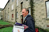 Postman delivering giro's before the post office shuts. Tenement housing on estate in Possil. Council flats boarded up but most still occupied. Glasgow housing stock due to transferred to private hous... - Jess Hurd - 18-09-1999