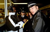 Police, another case of mistaken identity as they attempt to photo fit a black protester for disturbancies at July 18th (J18). Euston November 30th (N30). Anti World Trade Organisation (WTO), in solid... - Jess Hurd - 1990s,1999,activist,activists,adult,adults,against,BAME,BAMEs,black,BME,bmes,CAMPAIGN,campaigner,campaigners,CAMPAIGNING,CAMPAIGNS,capitalism,capitalist,CLJ crime law justice,DEMONSTRATING,DEMONSTRATI