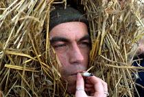 Whittlesey Straw Bear Man smoking. Cambridgeshire - James Jenkins - 11-01-2003