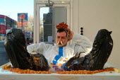 "Performance artist Mark McGowan performing his ""beans, chips & sausages"" at the House Gallery, Camberwell High Street, London. Sitting in a bath of baked beans for 12 days, he has two chips up his nos... - James Jenkins - 15-11-2003"