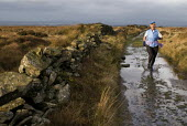 Woman running along a footpath on Wheelton Moor, near Brinscall, Lancashire - Paul Carter - 01-12-2007