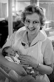 Auxiliary nurse with a newborn baby - Paul Carter - 1980s,1983,AUXILIARIES,auxiliary,babies,baby,care,child,CHILDHOOD,children,EARLY YEARS,EMOTION,EMOTIONAL,EMOTIONS,FEMALE,hea,HEA health,health,HEALTH SERVICES,healthcare,hospital,hospitals,infancy,inf