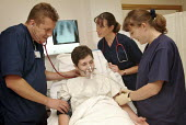 Nurse registrars training as nurse consultants, practise procedures with the help of a colleague volunteer. Accident and emergency unit. - Paul Carter - 11-08-2004