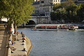 People relaxing in the sunshine, sunbathing, on a quayside on the banks of the River Seine. Quay dOrleans. A batobus tourist sightseeing boat passes. Paris. - Paul Carter - 19-09-2008