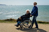 Elderly woman with her carer at Milford-on-Sea enjoy the sunshine and views across the sea. - Paul Carter - 25-07-2009