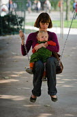 Mother and young son sitting on a swing in a city park. Paris - Paul Carter - 19-09-2008
