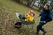 Two brothers having a ride in a wheelbarrow. They are being pushed by their father. - Paul Carter - ,2010,2010s,active,activity,autumn,AUTUMNAL,bonding,boy,boys,brother,brothers,child,CHILDHOOD,children,DAD,DADDIES,DADDY,DADS,EMOTION,EMOTIONAL,EMOTIONS,enjoy,ENJOYING,enjoyment,excited,exciting,famil