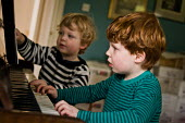 Two young boys playing the piano together in the front room at home. - Paul Carter - 27-09-2010