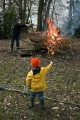 A young boy watches his father tending a garden bonfire. - Paul Carter - 27-09-2010