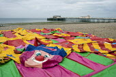 Deflated bouncy castle with Worthing Pier in the distance as the holiday season ends. Worthing, West Sussex UK. - Paul Carter - 29-09-2010