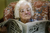 Elderly woman sitting in an armchair, reading a newspaper. - Paul Carter - 20-02-1996