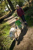 A young boy and his grandmother walk a pet dog through woodland in Norley Wood, The New Forest. - Paul Carter - 20-04-2011
