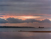 Sunset over still water with a cargo ship silhouetted on the horizon. - Paul Carter - 28-01-1999