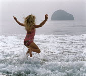 Young girl jumping in the waves on a beach. - Paul Carter - 1980s,1988,activity,beach,beaches,child,CHILDHOOD,children,COAST,coastal,coastline,coastlines,coasts,energy,ENI environmental issues,ENJOYING,enjoyment,holiday,holiday maker,holiday makers,holidaymake