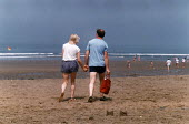 Couple walking hand-in-hand along a sandy beach. - Paul Carter - 1980s,1988,activity,adult,adults,bathing,beach,BEACHES,castles,coast,coastal,coastline,coastlines,coasts,Couple,COUPLES,ENI environmental issues,ENJOYING,enjoyment,families,family,female,flag,FLAGS,ho