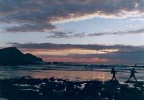 Childen playing on a beach at sunset. - Paul Carter - 1990,1990s,beach,BEACHES,breakers,calm,cliff,cliffs,cloud,clouds,coast,coastal,coastline,coastlines,coasts,destination,dusk,ENI environmental issues,enjoying,enjoyment,EVENING,fun,geology,headland,hol