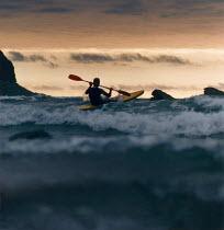 Lone canoeist paddling out to sea. - Paul Carter - 1990,1990s,boat,boats,breakers,calm,canoe,canoeing,canoes,cloud,clouds,coast,coastal,coastline,coastlines,coasts,craft,destination,dusk,ENI environmental issues,EVENING,geology,headland,holiday,holida