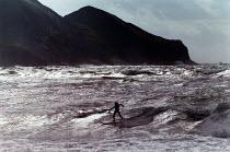 Surfer riding the waves. - Paul Carter - 1990s,1998,breakers,breaking,cliff,coast,coastal,coastline,coastlines,coasts,Extreme Sports,headland,holiday,holiday maker,holiday makers,holidaymaker,holidaymakers,holidays,landscape,LANDSCAPES,Leisu