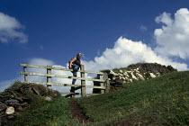 Walker climbs over a stile on the North Cornwall coastal path. - Paul Carter - 21-08-1997