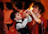 A young boy trying champagne from his mother's glass during a wedding reception. - Paul Carter - 1990s,1999,adult,adults,Alcohol,boy,boys,celebrate,CELEBRATING,celebration,CELEBRATIONS,champagne,CHAMPAIGN,child,CHILDHOOD,children,drink,drinker,drinkers,drinking,drinks,EMOTION,EMOTIONAL,EMOTIONS,E