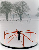 Roundabout and joggers in the snow. - Paul Carter - 1980s,1984,and,calm,cold,Council Services,Council Services,ENI environmental issues,equipment,exercise,exercises,jog,jogging,landscape,LANDSCAPES,local authority,merry go round,outdoors,outside,park,p