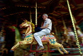 Man rides on a merry-go-round horse. - Paul Carter - 1980s,1989,ACE,ACE entertainment,adult,adults,age,ageing population,animal,animals,attraction,blur,culture,domesticated ungulate,domesticated ungulates,elderly,EMOTION,EMOTIONAL,EMOTIONS,ENJOYING,enjo
