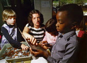 Teacher helping children learn about money. - Paul Carter - 1980s,1987,arithmetic,BAME,BAMEs,black,BME,bmes,boy,BOYS,child,CHILDHOOD,children,class,classroom,CLASSROOMS,coin,coins,communicating,communication,currencies,currency,diversity,EDU Education,ethnic,e