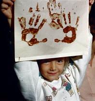 Young girl holding up a hand print painting. - Paul Carter - 1980s,1987,art,child,CHILDHOOD,children,class,craft,EDU Education,hands,infancy,infant,infants,juvenile,juveniles,kid,kids,lesson,LESSONS,paint,painting,people,picture,pictures,primary,Primary School,