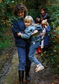 Teacher carrying a child through mud, during a nature walk. - Paul Carter - 1980s,1987,adult,ADULTS,assistant,ASSISTANTS,block,blocks,boots,boy,BOYS,carries,carry,carrying,child,CHILDHOOD,children,EDU Education,educational,EMOTION,EMOTIONAL,EMOTIONS,enjoying,enjoyment,female,