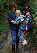Teacher carrying a child through mud, during a nature walk. - Paul Carter - 05-10-1987