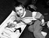 Small boy colouring. - Paul Carter - 1980s,1989,art,CARE,carer,carers,child,CHILD CARE,CHILDCARE,CHILD-CARE,CHILDHOOD,CHILDMINDING,CHILDREN,colouring-in,CRECH,creche,CRECHES,draw,drawing,EARLY,early years,EDU Education,feet,felt,floor,fo