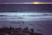 People watching the sunset on the beach. Crackington Haven, North Cornwall. - Paul Carter - 1990s,1992,beaches,breakers,calm,coast,coastal,coastline,coastlines,coasts,destination,dusk,ENI environmental issues,evening,exercise,exercises,foam,holiday,holiday maker,holiday makers,holidaymaker,h