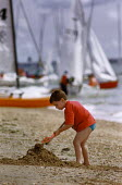 Young boy digging on a sandy beach. Yachts rigged up in the background. - Paul Carter - 01-08-1993